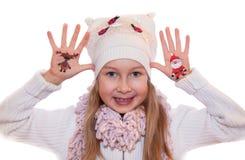 Muchacha feliz que demuestra los símbolos de la Navidad pintados en las manos Papá Noel y reno Imagen de archivo