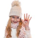 Muchacha feliz que demuestra los símbolos de la Navidad pintados en las manos Regalo y acebo Fotos de archivo libres de regalías