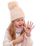 Muchacha feliz que demuestra los símbolos de la Navidad pintados en las manos Regalo y acebo Imagenes de archivo