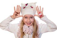 Muchacha feliz que demuestra los símbolos de la Navidad pintados en sus manos Imagen de archivo libre de regalías