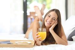 Muchacha feliz que desayuna con el zumo de naranja Imagen de archivo libre de regalías
