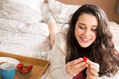 Muchacha feliz que desayuna en cama Fotos de archivo libres de regalías