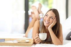 Muchacha feliz que desayuna que sostiene una taza de café Fotografía de archivo libre de regalías