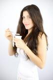 Muchacha feliz que desayuna sano con la consumición del yogur Imagen de archivo libre de regalías