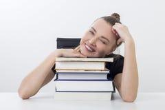 Muchacha feliz que descansa sobre una pila de libros Fotos de archivo