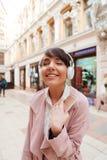 Muchacha feliz que disfruta de escuchar la música en una calle de la ciudad Fotografía de archivo libre de regalías