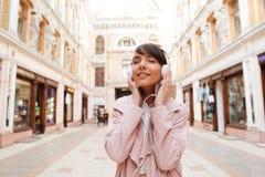 Muchacha feliz que disfruta de escuchar la música en una calle de la ciudad Fotografía de archivo