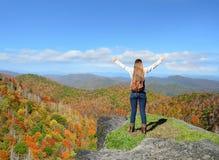 Muchacha feliz que disfruta de tiempo en viaje de la montaña Foto de archivo libre de regalías
