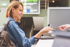 Muchacha feliz que entrega el pasaporte en aeropuerto Foto de archivo libre de regalías