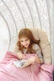 Muchacha feliz que entretiene con el libro en la hamaca Fotos de archivo libres de regalías
