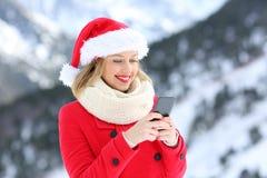 Muchacha feliz que envía mensajes de la Navidad en el teléfono Imagen de archivo libre de regalías