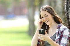 Muchacha feliz que escucha en la línea música en un parque Fotos de archivo libres de regalías