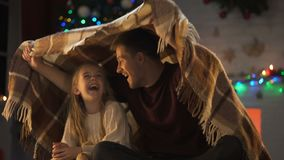 Muchacha feliz que escucha la historia del papá, sentándose debajo de la tela escocesa cerca de árbol chispeante de Navidad almacen de video