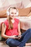 Muchacha feliz que escucha la música del smartphone Fotografía de archivo