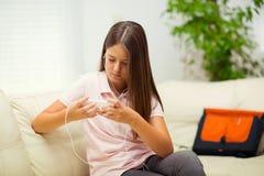 Muchacha feliz que escucha la música del teléfono móvil Imagen de archivo libre de regalías