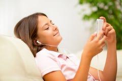 Muchacha feliz que escucha la música del teléfono móvil Fotografía de archivo