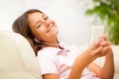 Muchacha feliz que escucha la música del teléfono móvil Foto de archivo libre de regalías