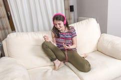 Muchacha feliz que escucha la música del teléfono móvil que se sienta en un cou Fotos de archivo