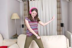 Muchacha feliz que escucha la música del teléfono móvil que se sienta en un cou Foto de archivo libre de regalías