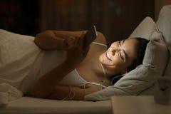 Muchacha feliz que escucha la música en la cama en la noche Fotos de archivo