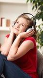 Muchacha feliz que escucha la música en el país Imagenes de archivo