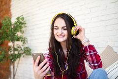 Muchacha feliz que escucha la música en línea de su smartphone que se sienta en el sofá en casa imagen de archivo