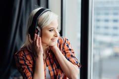 Muchacha feliz que escucha la música en la ventana Imagenes de archivo