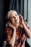 Muchacha feliz que escucha la música en la ventana Imágenes de archivo libres de regalías