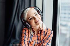Muchacha feliz que escucha la música en la ventana Fotos de archivo libres de regalías