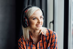 Muchacha feliz que escucha la música en la ventana Imagen de archivo