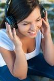 Muchacha feliz que escucha la música en los auriculares Imagenes de archivo