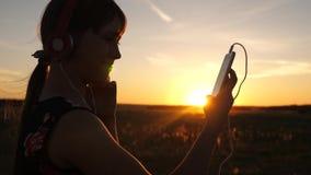 Muchacha feliz que escucha la música en un smartphone en los rayos de una puesta del sol hermosa Chica joven en auriculares y con almacen de video