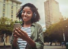 Muchacha feliz que escucha la música que hojea el contenido elegante del teléfono imagenes de archivo