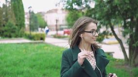 Muchacha feliz que escucha la música, sonriendo en la calle en el día ventoso 4k almacen de video