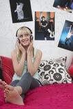 Muchacha feliz que escucha la música a través de los auriculares en cama Imagen de archivo libre de regalías