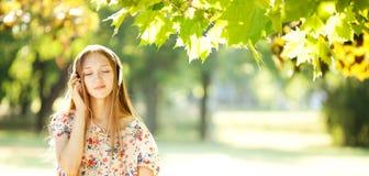 Muchacha feliz que escucha los auriculares en Autumn Day maravilloso Imagenes de archivo