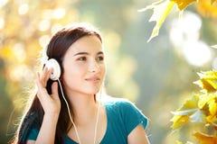 Muchacha feliz que escucha los auriculares en Autumn Day maravilloso Fotografía de archivo libre de regalías