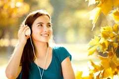 Muchacha feliz que escucha los auriculares en Autumn Day maravilloso Foto de archivo