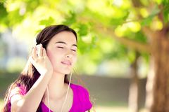 Muchacha feliz que escucha los auriculares en Autumn Day maravilloso Foto de archivo libre de regalías