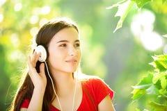 Muchacha feliz que escucha los auriculares en un día de verano maravilloso Imagenes de archivo