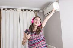 Muchacha feliz que escucha y que baila a la música del teléfono móvil en a Imagen de archivo libre de regalías