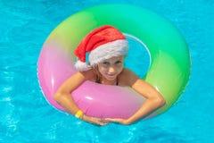 Muchacha feliz que flota en una piscina azul en los sombreros de Papá Noel en un fondo azul, mirada en la cámara y sonrisa Concep fotos de archivo