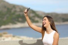 Muchacha feliz que fotografía un selfie en la playa Imagen de archivo libre de regalías