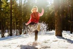 Muchacha feliz que golpea nieve con el pie Foto de archivo libre de regalías