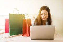 Muchacha feliz que hace compras en línea en la cama Imagen de archivo libre de regalías