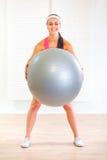 Muchacha feliz que hace ejercicios con la bola del ajuste Imagenes de archivo
