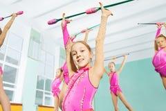 Muchacha feliz que hace ejercicios gimnásticos con los clubs Fotos de archivo
