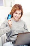 Muchacha feliz que hace en la línea compras con de la tarjeta de crédito Fotos de archivo libres de regalías