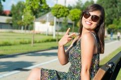 Muchacha feliz que hace gesto de la paz afuera en parque Fotografía de archivo