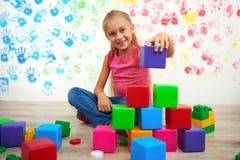 Muchacha feliz que hace la pirámide de cubos coloreados Foto de archivo libre de regalías